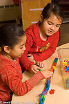 Preschool  vertical 4-5 year olds two girls talking and playing together with construction toy road and small plastic dinosaur toys