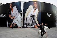 People walk past a huge billboard of Emporio Armani at Shin Kong Place, which is one of the most luxurious shopping centers in Beijing, having successfully attracted 938 international class brands, they also boast the largest Gucci flagship store in Asia..