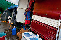 A Colombian boy enters his trailer at the Circo Anny, a family run circus wandering the Amazon region of Ecuador, 4 July 2010. The Circo Anny circus belongs to the old-fashioned traveling circuses with a usual mixture of acrobat, clown and comic acts. Due to the general loss of popularity caused by modern forms of entertainment such as movies, TV shows or internet, these small family enterprises balance on the edge of survival. Circuses were pushed away and now they have to set up their shows in more remote villages. The circus art and culture is slowly dying.