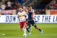 Jerry Bengtson (27) of the New England Revolution is marked by Brandon Barklage (25) of the New York Red Bulls. The New York Red Bulls defeated the New England Revolution 4-1 during a Major League Soccer (MLS) match at Red Bull Arena in Harrison, NJ, on March 20, 2013.