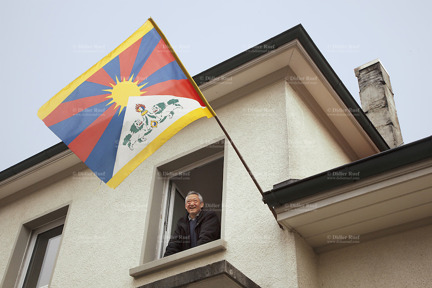 "Switzerland. Canton Bern. Muri. Thubten Purang at home with a tibetan flag. The swiss tibetan man is an Aeschimann's child who arrived 50 years ago in Switzerland to receive custody on a private initiative by an influential Swiss industrialist, Charles Aeschimann. In 1962, Charles Aeschimann agreed with the Dalai Lama to take 200 children and place them in Swiss foster homes and give them a chance for a better life and a good education. Most of the children still had parents in exile or in Tibet, just a few were orphans. The Tibetan flag, also known as the ""snow lion flag"" and the 'Free Tibet flag', was a flag of the military of Tibet, introduced by the 13th Dalai Lama in 1912 and used for the same capacity until 1959. Designed with the help of a Japanese priest, it reflects the design motif of the Japanese military's Rising Sun Flag. Since the 1960s, it is used a symbol of the Tibetan independence movement. 24.02.2015 © 2015 Didier Ruef"
