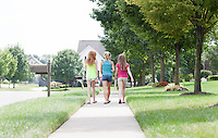 Three Young Girls Walking together in a  Residential Neighborhood.  Selective focus on the Children.