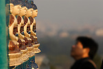 A visitor look at Buddha's statues on the White Pagoda in Beihai Park. Beijing. China