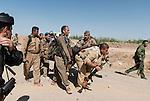 30/09/14  Iraq -- Daquq, Iraq -- Peshmerga fighters pick up a wounded comrade at the front line in Wahda village, Daquq.