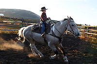 Tanner Lauman rides his buckskin, a trained mustang around in circles in the corral.