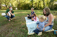 Marie Parks (from left), children's librarian at the West Fork Public Library, reads a book Tuesday, Sept. 7, 2021, about shearing sheep as Trish Jett and her daughter, Sophie Jett, 3, and Axyl White, 2, and his mother, Bethany White, all of Winslow, listen during story time in a clearing outside the library. Library staff took a break from hosting story time during August, but is back to hosting visitors at 10 a.m. on Tuesdays. Visit nwaonline.com/210908Daily/ for today's photo gallery.<br /> (NWA Democrat-Gazette/Andy Shupe)