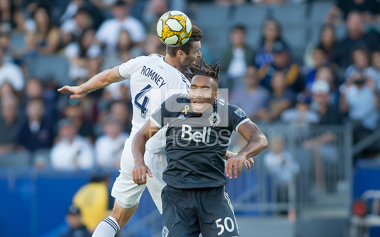 CARSON, CA - SEPTEMBER 29: Dave Romney #4 of the Los Angeles Galaxy and Theo Bair #50 of the Vancouver Whitecaps battle in the air for a ball during a game between Vancouver Whitecaps and Los Angeles Galaxy at Dignity Health Sports Park on September 29, 2019 in Carson, California.