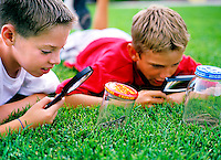 Two young boys with looking at bugs in a bottle with magnifying glass
