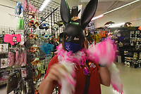 Amber Green of Bentonville tries on costume items Tuesday Oct. 13 2020 at Halloween Express at Frisco Station Mall in Rogers. Green shopped for a costume she'll wear to a murder mystery halloween party.<br />