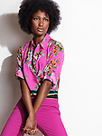 Beautiful young african american black woman wearing pink floral shirt and pants. Fashion photo isolated on white background. Image © MaximImages, License at https://www.maximimages.com