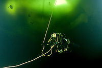 Scuba diver under ice and ice formation, Arctic circle Dive Center, White Sea, Karelia, northern Russia