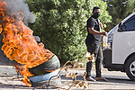 Sudanese protesters some clad in masks as a precaution due to the COVID-19 coronavirus pandemic, wave national flags and burn tyres as they take part in a demonstration in the capital Khartoum, on May 23, 2020. Scores of protesters were killed when armed men in military fatigues stormed the sprawling encampment outside Khartoum's army headquarters on June 3 last year. Photo by faiz Abu bakr
