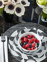 A table is laid for breakfast with black and white patterned tableware.