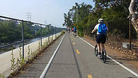 Heading south on the Los Angeles River Greenway Trail from Griffith Park at the start of the 2017 (17th annual) Los Angeles River Ride.  Many bicyclists can be seen ahead of Holland on his Yedoo kick scooter.  The river and its beautiful greenery can be seen to the left of the trail.