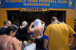 Mansfield Town Football Club Open Day, 14/07/2013. Field Mill stadium, League Two. Mansfield Town supporters trying on their team's new strips at a kiosk outside Field Mill stadium during an open day held for the club's supporters. Mansfield Town achieved promotion back to England's Football League by winning the Conference National in season 2012-13. Field Mill was the oldest ground in the Football League, hosting football since 1861 although some reports date it back as far as 1850, with Mansfield Town having played there since 1919. Photo by Colin McPherson.