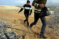 Two Palestinians run as they cross a barb wire fence in Kalandia, in the outskirts of Ramalah as they trie to avoid the Israeli army checkpoint March 11,2003. Photo by Quique kierszenbaum