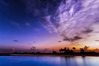 Colorful twilight on Tikehau atoll, with cloudy, starry sky over palm tree silhouettes, in Tuamotus Archipelago, French Polynesia, South Pacific Ocean