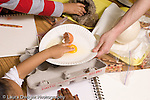 Preschool Headstart 3-5 year olds children doing guided observation and drawing comparing eggs from different mammals children touching opened chicken eggs