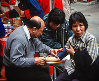 San Francisco, California, USA. Chinatown, Chinese New Year Street Market, Having Blood Pressure Checked.