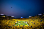 A U.S. Navy F/A-18F Hornet from Naval Air Station Oceana does a low flyover above Michigan Stadium, passing below a Goodyear airship, before an NCAA college football game between Washington and Michigan in Ann Arbor, Mich., Saturday, Sept. 11, 2021. (AP Photo/Tony Ding)
