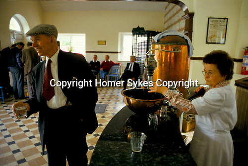 Old man drinking a glass of Sulphur Water, it is supposed to clear a hangover and cleanse the body. Lisdoonvarna County Clare Eire. 1990s.  They cost 10p per glass.