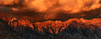 panoramic vew - dawn light turns the eastern sierras and storm clouds alpenglow pink in the alabama hills blm lands in california