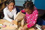 Preschool 3 year olds two girls playing together buiding with blocks