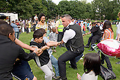 Police and Community Support Officers take part in a tug-of-war, Westbourne Festival, Westbourne Green.