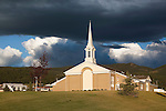 A sunlit church in Phillipsburg, Montana with dark clouds over head