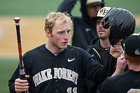 Jonathan Pryor (11) of the Wake Forest Demon Deacons is congratulated by teammates after scoring a run against the Towson Tigers at Wake Forest Baseball Park on March 1, 2015 in Winston-Salem, North Carolina.  The Demon Deacons defeated the Tigers 15-8.  (Brian Westerholt/Four Seam Images)