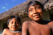 Koatinemo village, Brazil. Two young smiling Assurini Indian boys, one wearing a necklace.