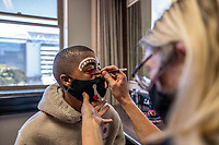 Ayabonga Tshofui, a student of the Cape Town College of Magic, has his face painted before a performance at the Artscape Theatre.