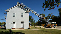 Ron Skelton (top), an assistant chief for the Springdale Fire Department, operates a ladder truck Tuesday, Oct. 13, 2020, to position Curtis Morris, exhibits manager for the Shiloh Museum of Ozark History, near the bell tower of the Shiloh Meeting Hall in Springdale so he can replace the mechanism that is used to ring the bell in the historic building. The original pre-Civil War-era bell is being curated in the museum's collection and a replacement has been fitted to the bell tower, but the mechanism to ring it needed to be improved. Visit nwaonline.com/201014Daily/ for today's photo gallery.