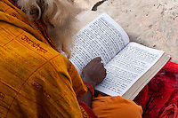Nepal, Pashupatinath.  Hindu Sadhu (Ascetic) Reading Hindu Scriptures.