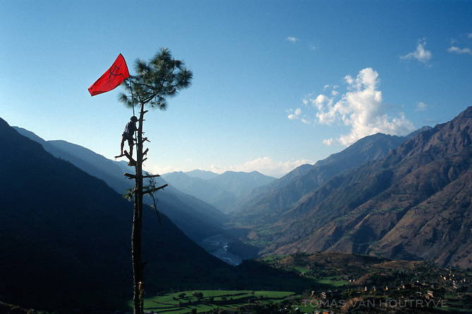 Nabin Pun, a Maoist rebel soldier of the People's Liberation Army, raises the communist flag from a tree above the village of Rukumkot, Nepal on Friday, 11 February 2005.