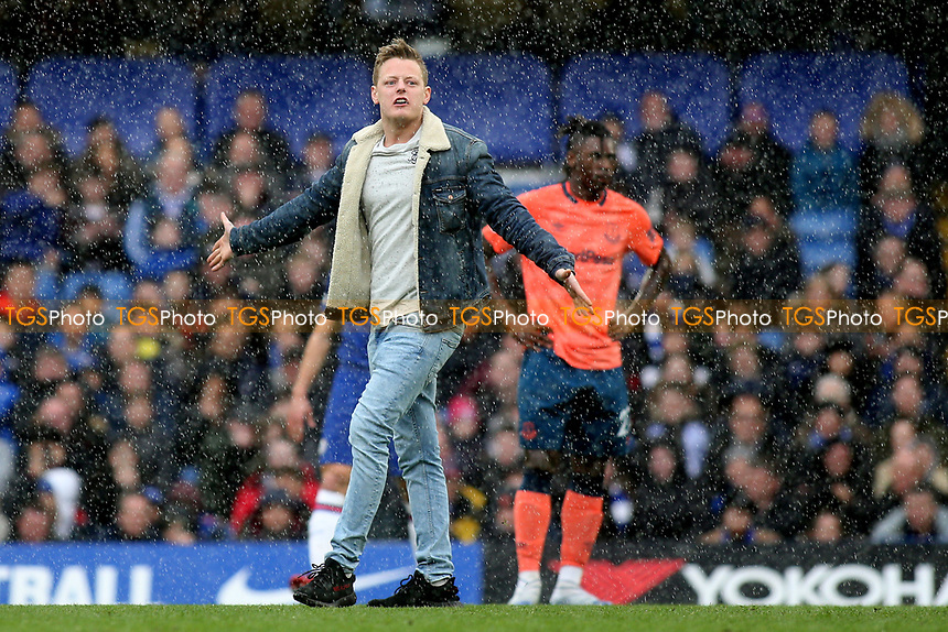A pitch invader leaves the shelter of the stand and runs onto the pitch while its pouring with rain during Chelsea vs Everton, Premier League Football at Stamford Bridge on 8th March 2020