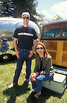 Couple relaxing in front of their vintage Ford Woody and travel trailer.