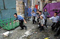"""Orthodox Jewish children chase a chicken in the orthodox neighborhood of Mea Shearim, Jerusalem September 10,2002. Religious Jews perform """"kaparot"""" rituals on the days before Yom Kippur. In this Jewish ritual performed ahead of the Day of Atonement, or Yom Kippur, the holiest day in the Jewish year, it is believed that one's sins from the past year are transferred to the chicken. The bird is then slaughtered and given to the poor. (Photo by Quique Kierszenbaum"""