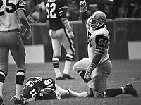 George Wells Hamilton Tiger Cats with injured Rick Cassata Ottawa Rough Riders quarterback 1972. Copyright photograph Scott Grant