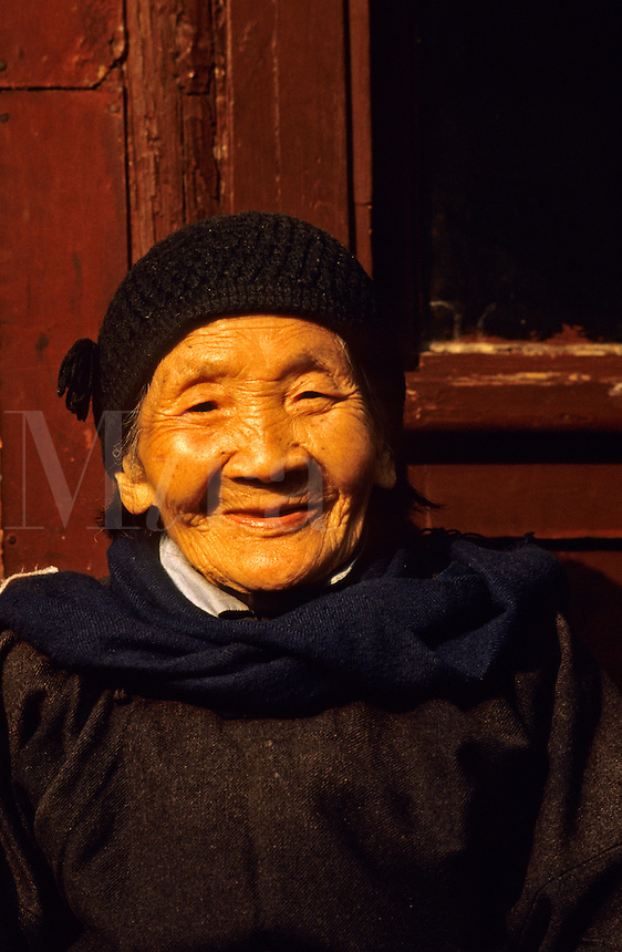 China. Old Chinese woman relaxing in the sun outside.