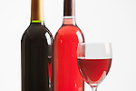 Two Bottles of Red Wine and Glass  White background.