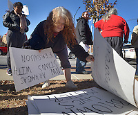 STAFF PHOTO BEN GOFF  @NWABenGoff -- 11/25/14 April Springfield picks out a sign to hold during a protest organized by the OMNI Center for Peace, Justice & Ecology in front of the Washington County Courthouse in Fayetteville on Tuesday Nov. 25, 2014. The demonstration was in response to the decision Monday night by the St. Louis County grand jury not to indict police officer Darren Wilson, who fatally shot Michael Brown in Ferguson, Mo.
