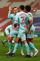 Kyle Naughton of Swansea City (C) is embraced by team mates Connor Roberts (L) and Korey Smith (R) after winning a penalty during the Sky Bet Championship match between Stoke City and Swansea City at the Bet365 Stadium, Stoke on Trent, England, UK. Wednesday 03 March 2021