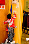 Education Preschool 3-4 year olds class job boy turning on and off light switch to signal time for clean up vertical.standing on step stool vertical