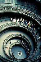 A group of tourists or visitors go up an impressive, spiral, winding staircase leading to the upper floors of the Vatican Museum. The Pope, highest authority of the Catholic Church, resides in the Vatican. Rome, Italy.