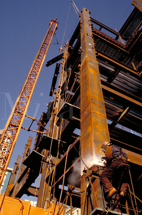 Construction worker welding a steel support on a new building. occupations. California.