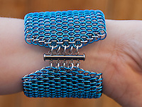 """A blue and silver dragonscale weave maille bracelet on  a wrist, focusing on the clasp.  It's made from saw cut 18 gauge 1/4"""" ID blue anodized aluminum rings and saw cut 19 gauge 5/32"""" ID bright aluminum rings.  The clasp is a gunmental plated slide clasp.   Handmade by Michelle."""