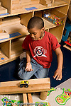 Education Preschool 4-5 year olds boy rolling toy vehicle down ramp he make out of wooden block vertical