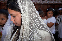 Antigua, Guatemala.  Semana Santa (Holy Week).  Woman in Scarf Accompanying Young Girls Carrying  an Anda (Float) in a Religious Procession.
