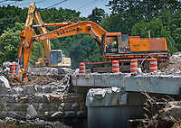 After removing the original roadway leading to the Main Street Bridge in Westerville, Ohio, workers begin demolition of the bridge structure.